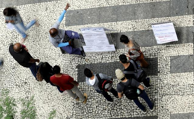 People look at lists of job openings posted on a street. January 9, 2018. REUTERS/Paulo Whitaker
