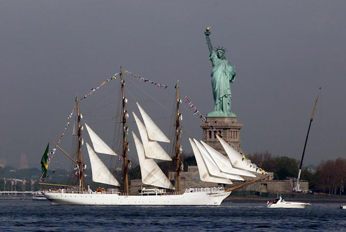 The Cisne Branco, from Brazil, sails by the Statue Of Liberty, in New York, to participate in Fleet Week activities, Wednesday, May 23, 2012. This year's event marks the bicentennial of the War of 1812. (AP Photo/Richard Drew)