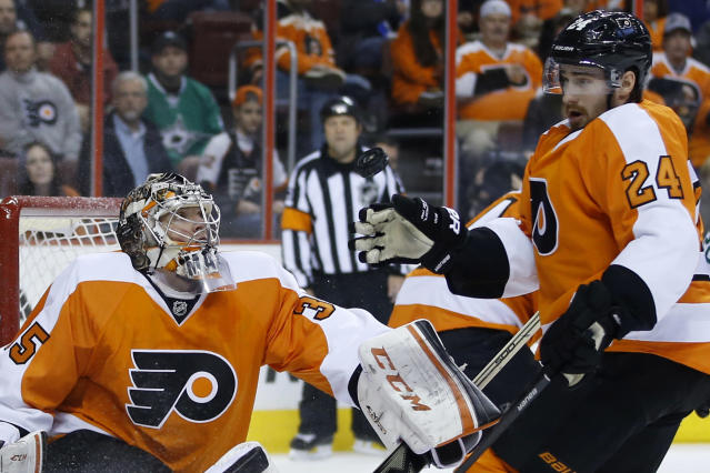 Philadelphia Flyers' Steve Mason, left, and Matt Read try to knock down a loose puck during the first period of an NHL hockey game against the Dallas Stars, Thursday, March 20, 2014, in Philadelphia. (AP Photo/Matt Slocum)