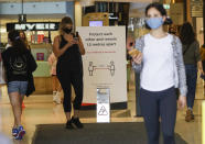 Shoppers wear masks as they walk around a shopping centre in Sydney, Australia, Sunday, Jan. 3, 2021. Masks have been made mandatory in shopping centers, on public transport, in entertainment venues such as a cinema, and fines will come into effect on Monday as the state government responds to the COVID-19 outbreak on Sydney's northern beaches, which is suspected to have also caused new cases in neighboring Victoria state. (AP Photo/Mark Baker)