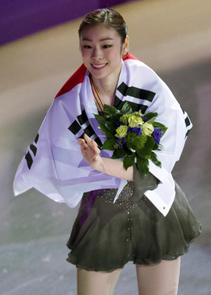 Gold medalist Kim Yu-na of South Korea greets fans on a victory lap after winning the ladies competition at the ISU World Figure Skating Championshipsin London, Ontario on Saturday March 16, 2013. (AP Photo/The Canadian Press, Frank Gunn)