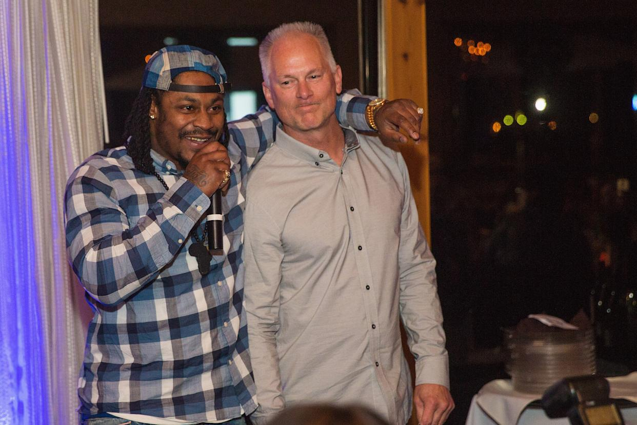 SEATTLE, WA - DECEMBER 14:  Marshawn Lynch (L) and Kenny Mayne speak during the FAM 1st FAMILY FOUNDATION Charity Event at The Edgewater Hotel on December 14, 2014 in Seattle, Washington.  (Photo by Mat Hayward/Getty Images for 1st Family Foundation)