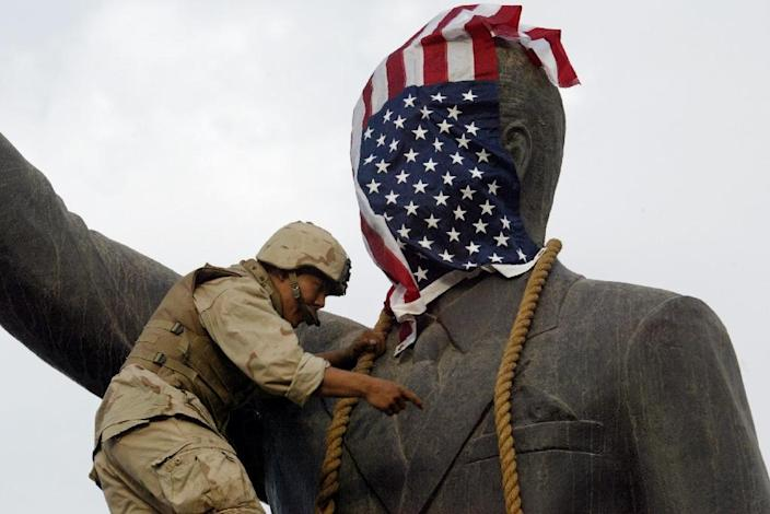 A US Marine covers the head of a statue of Iraqi President Saddam Hussein with the US flag on April 9, 2003 before it is toppled (AFP Photo/RAMZI HAIDAR)