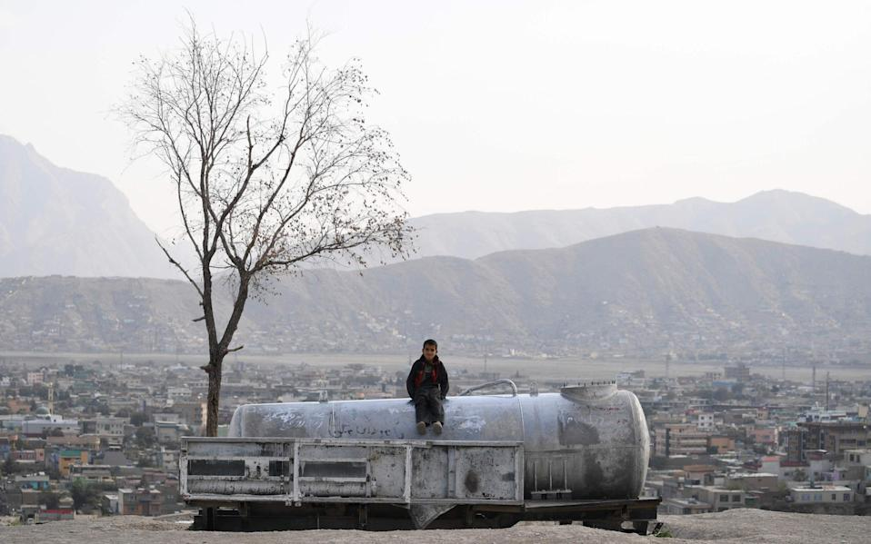 An Afghan child sits on a water tank at Nadir Khan hill in Kabul on October 1, 2019. (Photo by Sajjad HUSSAIN / AFP)SAJJAD HUSSAIN/AFP/Getty Images - AFP