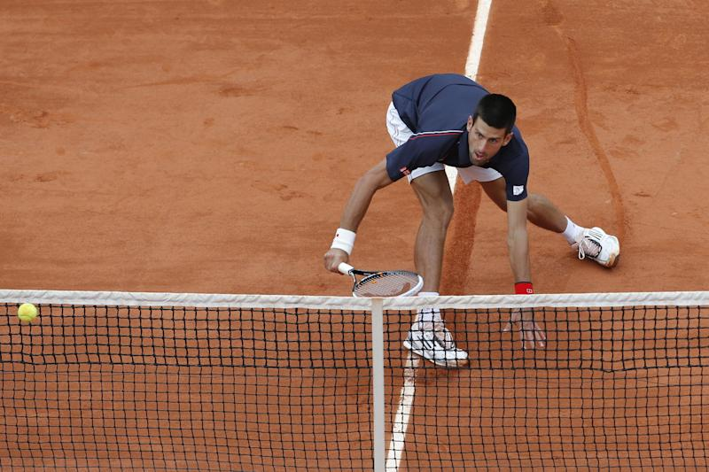 Novak Djokovic of Serbia slides to the net to return in his fourth round match against Andreas Seppi of Italy at the French Open tennis tournament in Roland Garros stadium in Paris, Sunday June 3, 2012. (AP Photo/Bernat Armangue)
