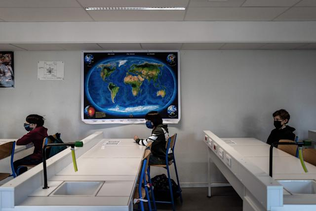 Pupils in protective face masks attend a lesson in a classroom at a school in Lyon, France, on Monday. (AFP via Getty Images)