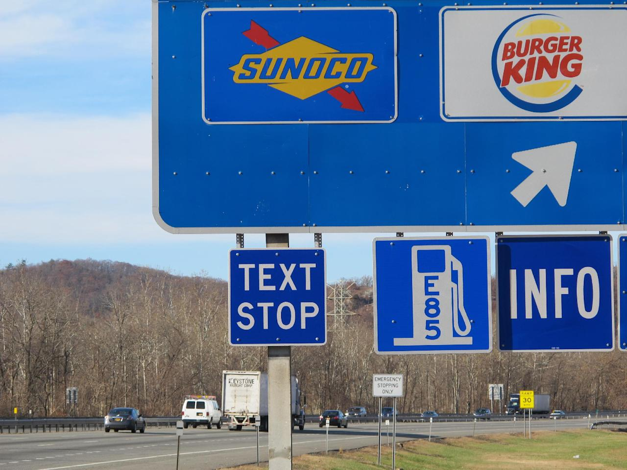 """A new """"text stop"""" notification is seen on a sign for a service area on the New York State Thruway in Sloatsburg, N.Y., on Thursday, Nov. 14, 2013. A state crackdown on texting while driving includes designating many pull-off areas as text stops. (AP Photo/Jim Fitzgerald)"""