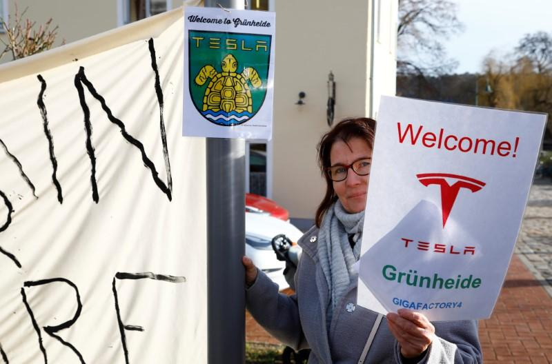 A demonstrators holds pro-Tesla poster during an action to support plans by U.S. electric vehicle pioneer Tesla to build its first European factory and design center in Gruenheide