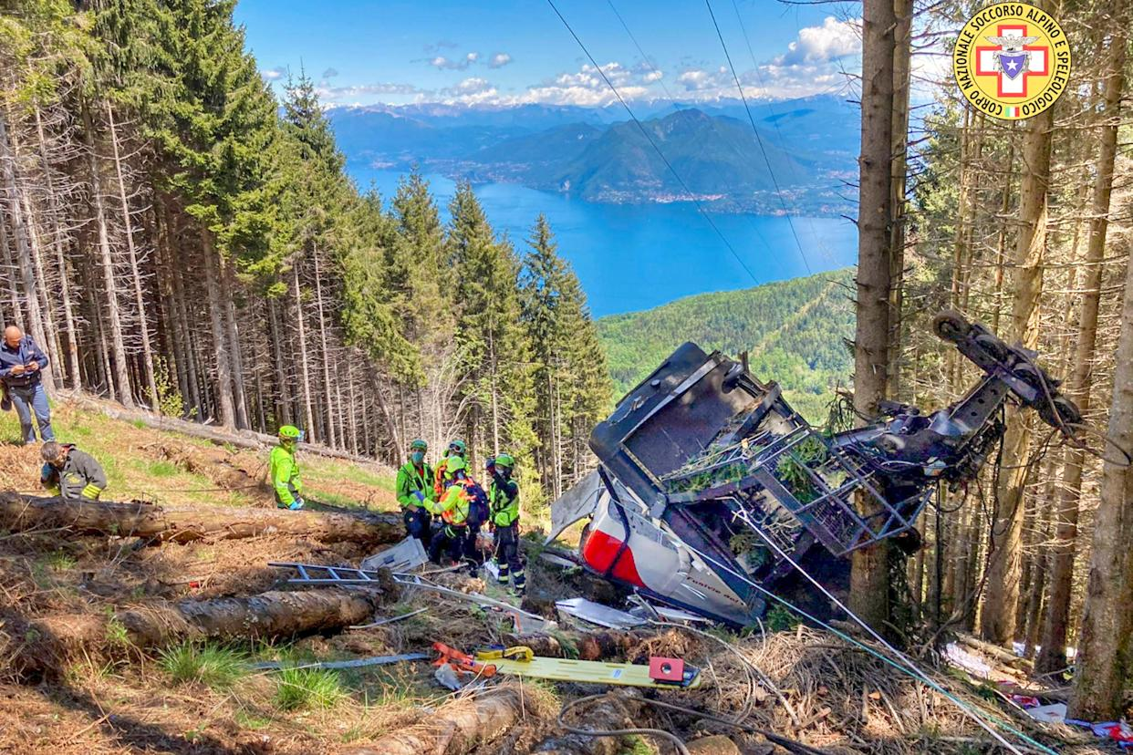 Rescuers work by the wreckage of a cable car after it fell near the summit of the Stresa-Mottarone line in the Piedmont region, northern Italy, Sunday, May 23.