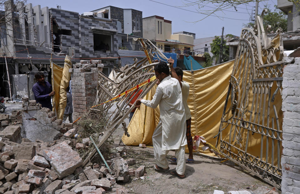 Residents remove a gate from their damaged house at the site of a car bombing Wednesday, in Lahore, Pakistan, Thursday, June 24, 2021. Pakistani security forces on Thursday arrested one of the alleged perpetrators of the car bombing that killed at least three people and wounded some 25 others near the residence of a jailed anti-India militant leader Hafiz Saeed, in the eastern city of Lahore, officials said. (AP Photo/K.M. Chaudary)