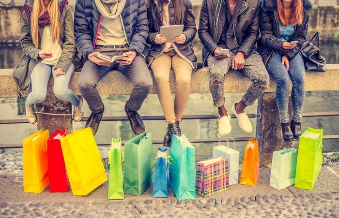 Several people sitting on a wall with shopping bags in front of them.