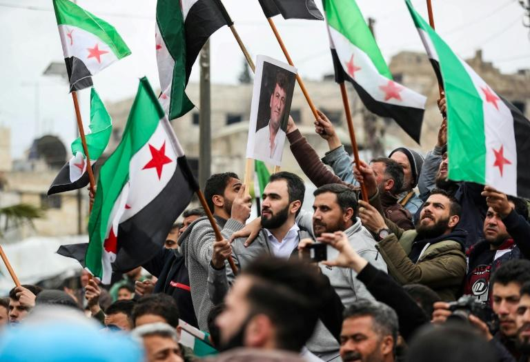 Syrian protesters wave the three-star flag of the opposition in Maaret al-Numan on March 15, 2019 (AFP Photo/OMAR HAJ KADOUR)