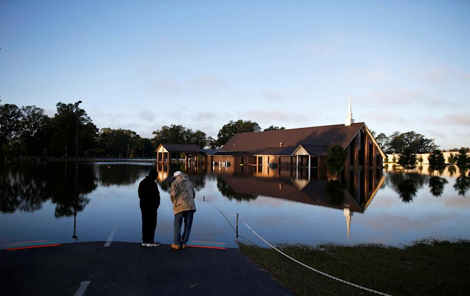 Steven Broadhurst (L) and Deacon Junius Shealy stand along the edge of the flood zone at St. Mark Church of Christ after the effects of Hurricane Matthew in Goldsboro, North Carolina, U.S., October 12, 2016. REUTERS/Randall Hill