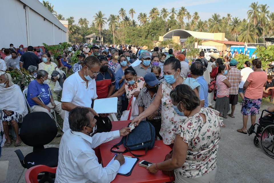COYUCA DE BENITEZ, MEXICO - APRIL 15: People give their information prior to receive a dose of the CanSino vaccine as part of COVID-19 vaccination on April 15, 2021 in Coyuca de Benitez, Mexico. Vaccination begins today in the regions of Tierra Caliente and some municipalities of Costa Grande, where health authorities will apply the vaccine CanSino, which is a single dose to adults over 60 years of age. (Photo by Karen Melo/gencia Press South/Getty Images)