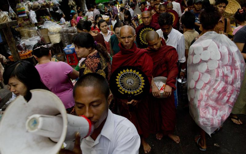 A Buddhist devotee uses a loudspeaker to announce the arrival of Buddhist monks expecting donations in a street market in Yangon, Myanmar, Tuesday, March 26, 2013. Myanmar's government warned Monday that religious violence could threaten democratic reforms after anti-Muslim mobs rampaged through three more towns in the country's predominantly Buddhist heartland. The mobs destroyed mosques and burned dozens of homes over the weekend despite attempts by the government to stem the nation's latest outbreak of sectarian violence. (AP Photo/Gemunu Amarasinghe)