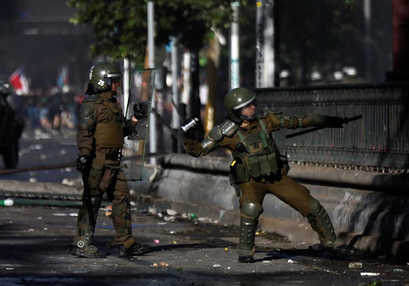 A member of the security forces throws a tear gas canister during an anti-government protests in Santiago, Chile on Oct. 28, 2019. (Photo: Edgard Garrido/Reuters)