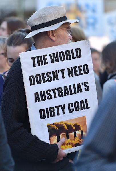 A man holds a placard during the climate rally in Melbourne (AFP Photo/Paul Crock)