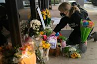 Shelby Swan adjusts flowers and signs outside Youngs Asian Massage where four people were shot and killed in Acworth, Georgia