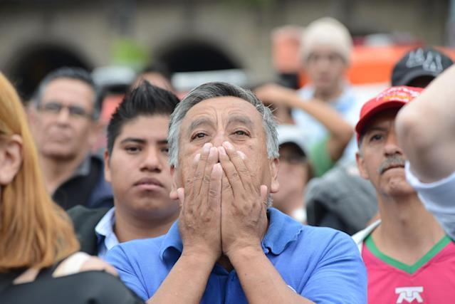 A Mexico soccer fan reacts to a near goal while watching his team's World Cup soccer match with Brazil on a large screen set up at the Zocalo in Mexico City, Tuesday June 17, 2014. Mexico claimed a deserved point against Brazil in a largely frustrating Group A game which finished 0-0 at Estadio Castelao in Fortaleza, Brazil. (AP Photo/Sean Havey)