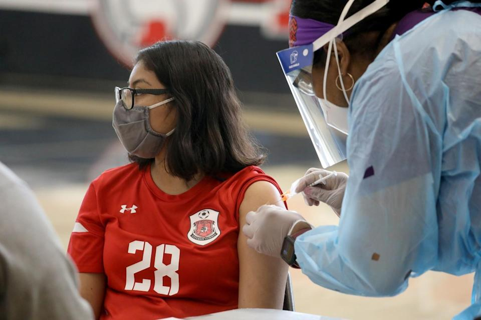 A masked teenager in glasses and a red shirt gets a shot in the arm from a health worker