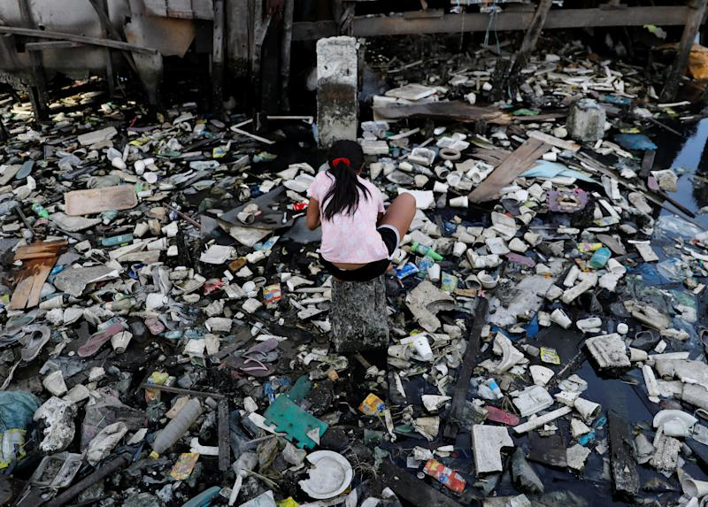 A girl plays in a garbage-filled river in Navotas, metro Manila, Philippines January 15, 2018.   REUTERS/Dondi Tawatao