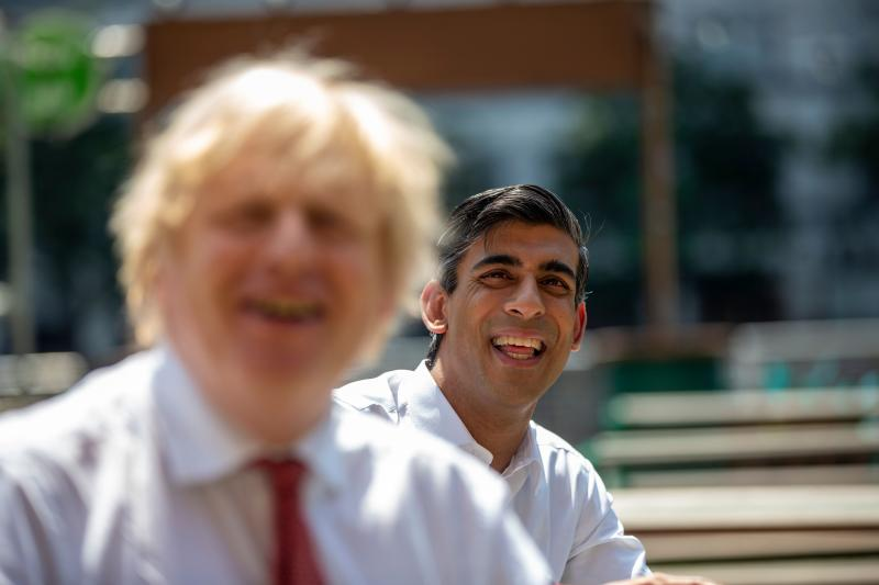Britain's Prime Minister Boris Johnson (L) reacts as he visits Pizza Pilgrims in West India Quay, London Docklands on June 26, 2020 with Britain's Chancellor of the Exchequer Rishi Sunak (R) as the restaurant prepares to reopen on July 4 as coronavirus lockdown rules are eased. - The British government on Thursday unveiled plans to get the public out of indoor confinement and on to the streets to boost the economy after three months of coronavirus lockdown. Prime Minister Boris Johnson wants pubs and restaurants to be buzzing in the curtailed summer season, despite continued social distancing rules and restrictions. (Photo by Heathcliff O'Malley / POOL / AFP) (Photo by HEATHCLIFF O'MALLEY/POOL/AFP via Getty Images)