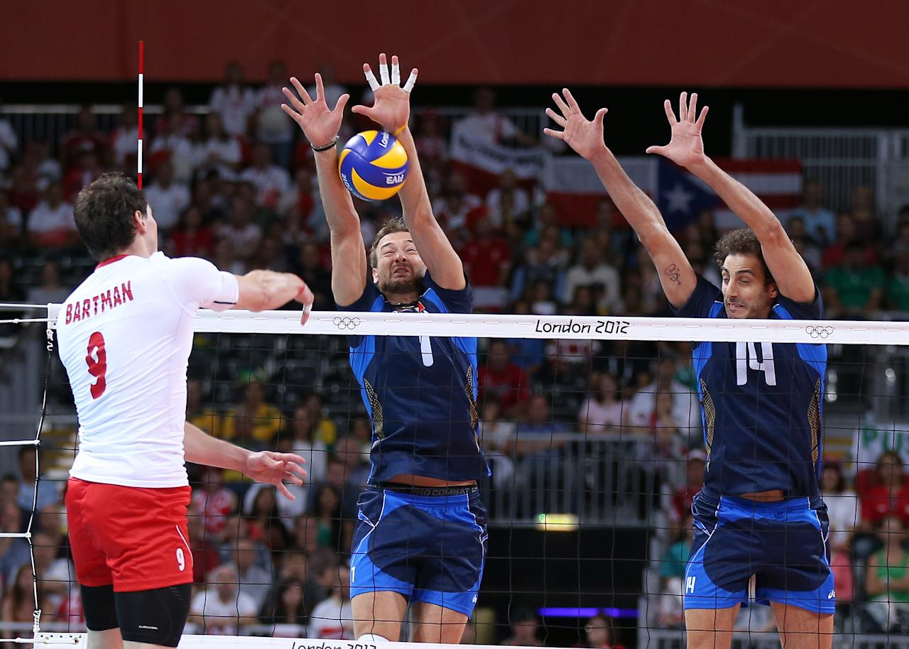 LONDON, ENGLAND - JULY 29:  Michal Lasko #7 and Alessandro Fei #14 of Italy try to stop a shot by Zbigniew Bartman #9 of Poland during Men's Volleyball on Day 2 of the London 2012 Olympic Games at Earls Court on July 29, 2012 in London, England.  (Photo by Elsa/Getty Images)