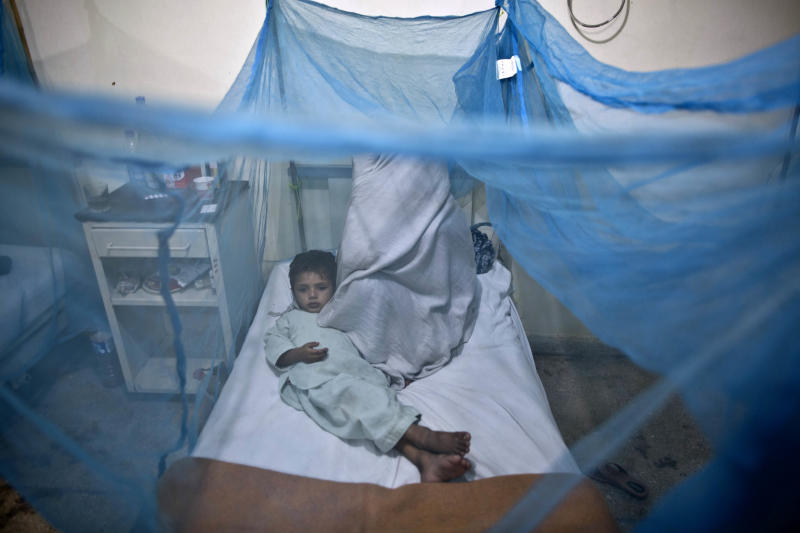 FILE - In this file photo taken Monday, Nov. 11, 2013, a Pakistani child suffering from the mosquito-borne disease, dengue fever, lies in a bed, next to his mother, covered with a net at an isolation ward of a hospital in Rawalpindi, Pakistan. Anita Zaidi, a Pakistani doctor, won a $1 million grant Tuesday, Dec. 10, to fight early child mortality in a small fishing village in southern Pakistan in a contest financed by an American entrepreneur to find innovative ways to save lives, The Caplow Children's Prize said. (AP Photo/Muhammed Muheisen, File)