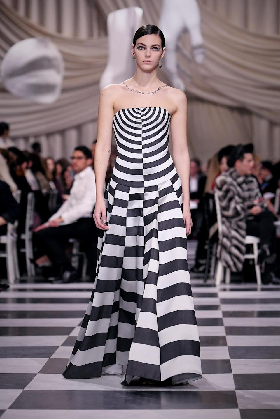 <p>A model wears a strapless mismatched black and white checkered and bull's-eye patterned dress from the Dior Haute Couture SS18 collection. (Photo: Getty) </p>
