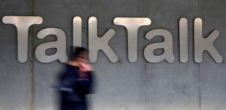 File photograph of a man walking past a company logo outside a TalkTalk building in London
