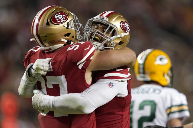 San Francisco 49ers defensive end Arik Armstead, center, is congratulated by defensive end Nick Bosa, left, after sacking Green Bay Packers quarterback Aaron Rodgers (12) during the first half of an NFL football game in Santa Clara, Calif., Sunday, Nov. 24, 2019. (AP Photo/Tony Avelar)