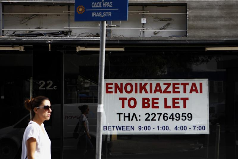 "A woman walks past an empty shop with ""Rent"" Sign displayed in central capital Nicosia, Cyprus, Thursday, Nov. 7, 2013. Cyprus' finance minister says that international creditors' second review of the country's bailout program has found that the required reforms are on track and that no new measures are needed to meet fiscal targets. (AP Photo/Petros Karadjias)"