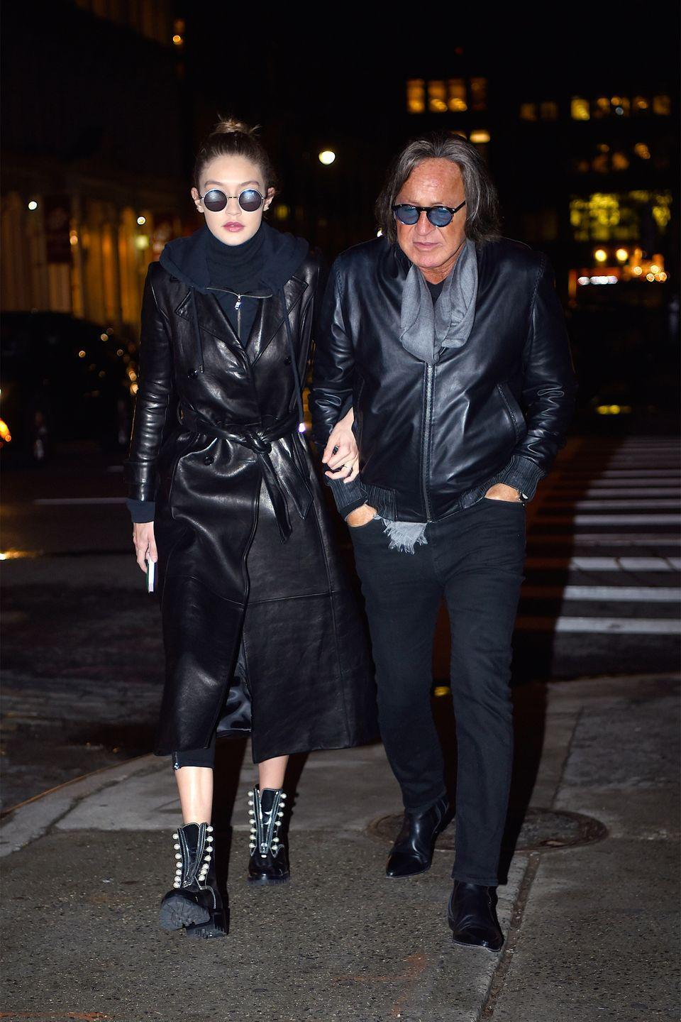 <p>In a navy hooded sweatshirt under a black leather trench coat by Frame with round sunglasses and studded combat boots while out in New York City with her father.</p>