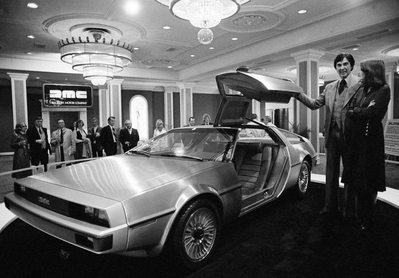 John Z. Delorean and his wife Christina, of Detroit, stand by his prototype car, Model 12, that was unveiled in New Orleans, La., Jan. 31, 1977. The brushed steel and fiber glass sports car is scheduled for production in 1979 with a six-cylinder engine, reported to get 30 miles per gallon on the highway. The cost: around $10,000. (AP Photo/Jack Thornell)
