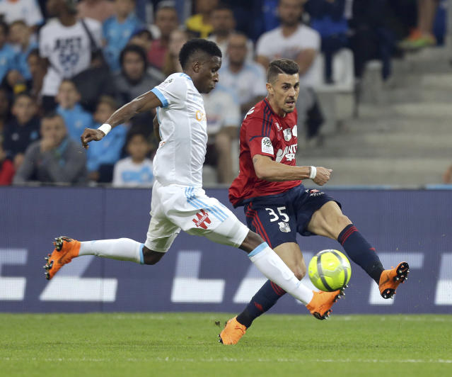 Marseille's Bouna Sarr, left, challenges for the ball with Amiens'Danilo Avelar, during the League One soccer match between Marseille and Amiens at the Velodrome stadium, in Marseille, southern France, Saturday, May 19, 2018. (AP Photo/Claude Paris)