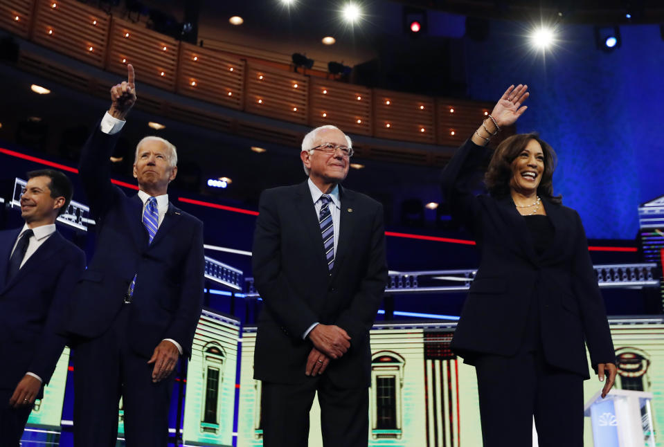 Democratic presidential candidates from left, South Bend Mayor Pete Buttigieg, former vice president Joe Biden, Sen. Bernie Sanders, I-Vt., and Sen. Kamala Harris, D-Calif., gesture before the start of the Democratic primary debate hosted by NBC News at the Adrienne Arsht Center for the Performing Arts, Thursday, June 27, 2019, in Miami. (AP Photo/Brynn Anderson)