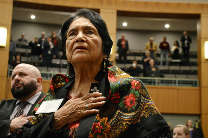 FILE - In this Feb. 27, 2019, file photo, Dolores Huerta, the Mexican-American social activist who formed a farmworkers union with Cesar Chavez, stands for the Pledge of Allegiance in Spanish while visiting the New Mexico Statehouse in Santa Fe, N.M. Immigrant rights activists energized by a new Democratic administration and majorities on Capitol Hill are gearing up for a fresh political battle to push through a proposed bill from President Joe Biden that would open a pathway to citizenship for up to 11 million people. Huerta said the immigration reform push will benefit from the dramatic stories of children being separated from their parents under the Trump administration. (AP Photo/Russell Contreras, File)