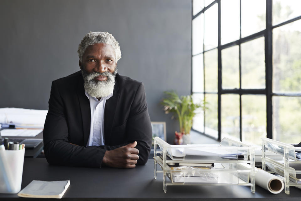 Portrait of confident businessman with arms crossed sitting at desk in modern office