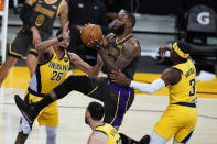 Los Angeles Lakers forward LeBron James, center, drives to the basket between Indiana Pacers guard Jeremy Lamb, left, and guard Aaron Holiday (3) during the first half of an NBA basketball game Friday, March 12, 2021, in Los Angeles. (AP Photo/Marcio Jose Sanchez)