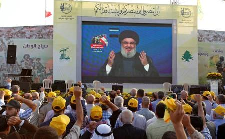 Lebanon's Hezbollah leader Sayyed Hassan Nasrallah gestures as he addresses his supporters via a screen during a rally marking the anniversary of the defeat of militants near the Lebanese-Syrian border, in al-Ain village