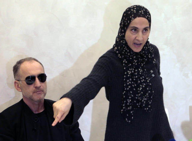 Zubeidat Tsarnaeva, the mother of the two Boston bombing suspects, speaks at a news conference as the suspects' father, Anzor Tsarnaev listens in Makhachkala, in the southern Russian province of Dagestan, Thursday, April 25, 2013. Anzor Tsarnaev said Thursday that he is leaving Russia for the United States in the next day or two, but their mother said she was still thinking it over. (AP Photo/Musa Sadulayev)