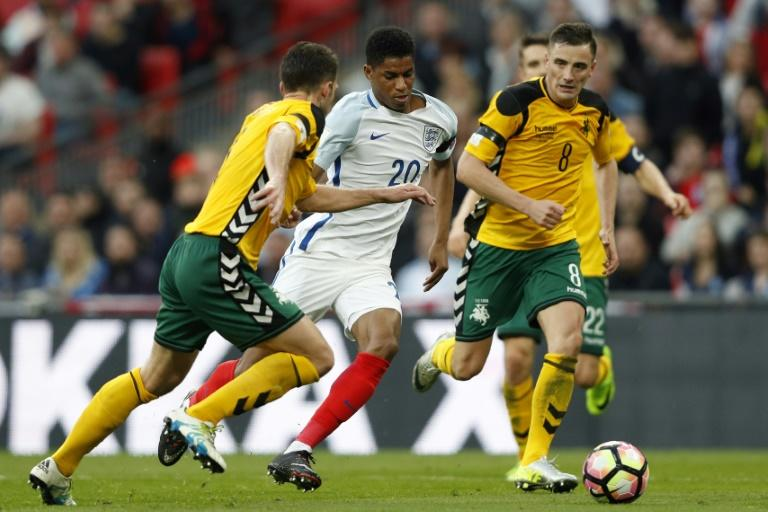 England's striker Marcus Rashford (C) runs through the challenges from Lithuania's defenders Tadas Kijanskas and Lithuania's Egidijus Vaitkunas (R) during a World Cup 2018 qualification match at Wembley Stadium