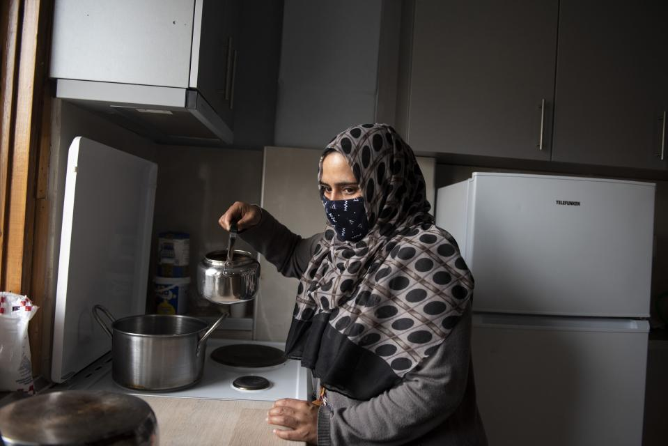 Kariman, 32, prepares tea at her family's apartment in the northern city of Thessaloniki, Greece, Saturday, May 1, 2021. Sundered in the deadly chaos of an air raid, a Syrian family of seven has been reunited, against the odds, three years later at a refugee shelter in Greece's second city of Thessaloniki. (AP Photo/Giannis Papanikos)