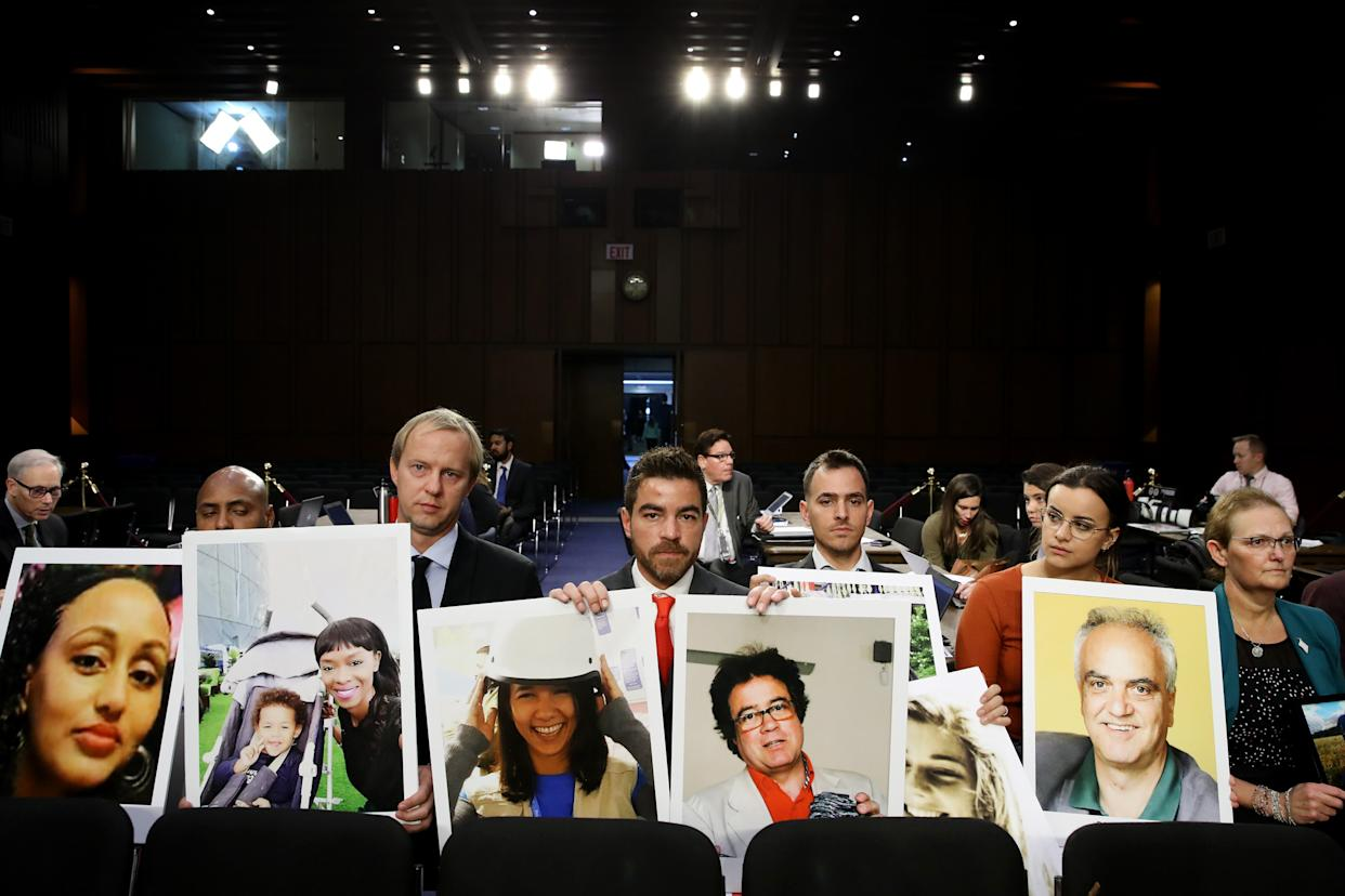 Image: BFamily members of victims of the Ethiopian Airlines crash sit with photos of their loved ones during testimony from Boeing CEO Dennis Muilenburg in Washington on Oct. 29, 2019.