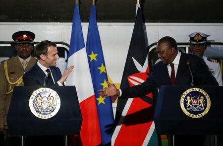 FILE PHOTO: French President Emmanuel Macron greets Kenya's President Uhuru Kenyatta as they address a news conference after touring the Nairobi Central Railway in Nairobi, Kenya March 13, 2019. REUTERS/Thomas Mukoya/File Photo