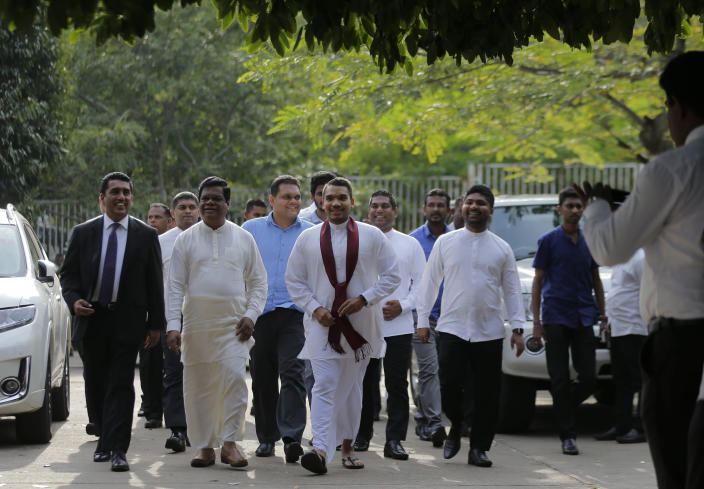 Namal, center wearing a red scarf, a Sri Lankan lawmaker and elder son of disputed Prime Minister Mahinda Rajapaksa, arrives with other lawmakers at the supreme court complex in Colombo, Sri Lanka, Thursday, Dec. 13, 2018. Sri Lanka's Supreme Court unanimously ruled as unconstitutional President Maithripala Sirisena's order to dissolve Parliament and call for fresh elections, a much-anticipated verdict Thursday that further embroils the Indian Ocean island nation in political crisis. (AP Photo/Eranga Jayawardena)
