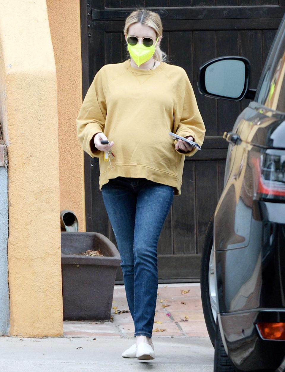 <p>Emma Roberts wore a yellow sweater, jeans and a neon yellow mask as she went about her day on Monday in L.A.</p>