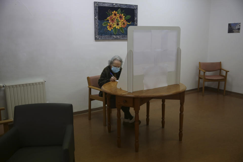 Rosa Gordo, 89, marks her presidential election ballot behind a makeshift voting booth at the elderly care home where she resides in Montijo, south of Lisbon, Tuesday, Jan. 19, 2021. For 48 hours from Tuesday, local council crews are collecting the votes from people in home quarantine and from residents of elderly care homes ahead of Sunday's presidential election. (AP Photo/Armando Franca)