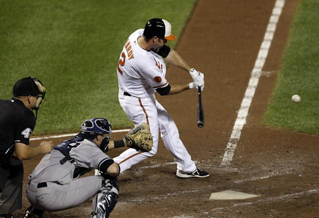 Baltimore Orioles' J.J. Hardy doubles in front of New York Yankees catcher Chris Stewart and home plate umpire Jeff Nelson in the fourth inning of a baseball game, Wednesday, Sept. 11, 2013, in Baltimore. Danny Valencia scored on the play. (AP Photo/Patrick Semansky)