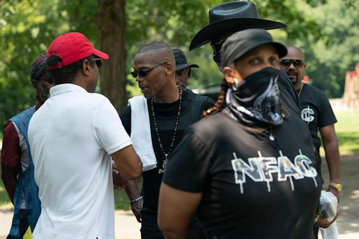 """July 24, 2021; Louisville, KY, USA;  John Fitzgerald Johnson, known as ÒGrandmaster Jay,"""" greets members and supporters of the Not Fucking Around Coalition (NFAC) as members of his security team stand nearby during the """"Feed the People"""" event at Chickasaw Park, Saturday July 24, 2021 in Louisville, KY.. Mandatory Credit: Jessica Koscielniak-USA TODAY"""